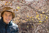 Smiling handsome young man outdoors in woodland — Stok fotoğraf