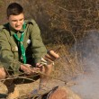 Young scout cooking his lunch over a fire — Stock Photo #57550901