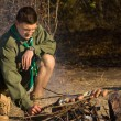 Young Male Scout Grilling Sausages at the Camp — Stock Photo #57550925