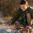 Young Boy Scout Cooking for Food on the Ground — Stock Photo #57550965