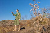 Scout standing on a rock taking a compass reading — Stock Photo