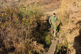 Scout crossing a narrow footbridge over a stream — Stock Photo