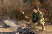 Park ranger cooking sausages — Stock Photo