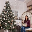 Sitting woman with presents near Christmas tree — Stock Photo #58732699