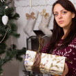 Serious Woman Holding Gift Box Near Christmas Tree — Stock Photo #58732835