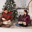 Young couple unwrapping their Christmas gifts — Zdjęcie stockowe #58732855