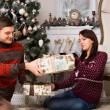 Young man giving his girlfriend a Christmas gift — Stock Photo #58732875