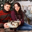 Young Couple Sitting on the Floor Holding One Gift — Stock Photo #58733047