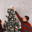 Man placing an ornament on top of a Christmas tree — Stock Photo #58733363