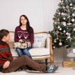 Sitting Young Couple Near Christmas Tree — Stock Photo #58733417