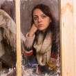 Sad young woman in a winter cabin — Stockfoto #58733651