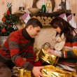 Young man and woman opening Christmas gifts — Stock Photo #58733929