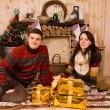 Couple celebrating Christmas in a rustic cabin — Stock Photo #58733941