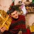 Young man guessing at his Christmas gift — Stock Photo #58734015