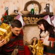 Young man and woman opening their Xmas gifts — Stock Photo #58734075