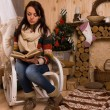 Woman Reading Book in Chair in Rustic Cabin — Stock Photo #58738311