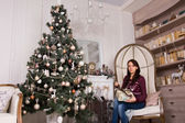 Sitting woman with presents near Christmas tree — Стоковое фото