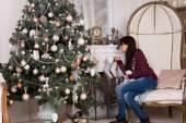 Young woman hanging Christmas stockings — Stock Photo