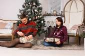 Young couple unwrapping their Christmas gifts — Стоковое фото