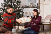 Young man giving his girlfriend a Christmas gift — Стоковое фото