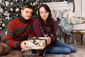 Young Couple Sitting on the Floor Holding One Gift — Стоковое фото