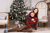 Woman Hugging Smiling Man Near Christmas Tree — Стоковое фото