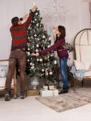 Young man and woman decorating for Christmas — Stock Photo