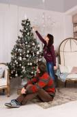 Young man watching his girlfriend decorate a tree — Stock Photo