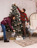 Young couple decorating the Christmas tree — Stockfoto