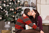 Romantic couple kissing in front of a Xmas tree — Stock Photo