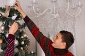 Happy young man decorating a Christmas tree — Стоковое фото