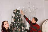 Couple placing the last ornament on a Xmas tree — Стоковое фото