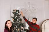 Smiling young couple decorating for Xmas — Stock Photo