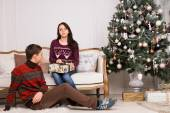 Sitting Young Couple Near Christmas Tree — Stock Photo