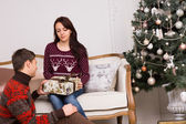 Young Sweethearts Holding Gift Near Christmas Tree — 图库照片
