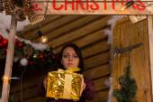 Serious Young Woman Giving a Golden Gift Box — Стоковое фото