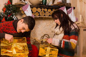 Young couple opening festive gold Xmas gifts — Stock Photo