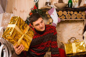 Young man guessing at his Christmas gift — Stok fotoğraf