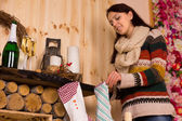 Young woman filling Christmas stockings — Stock Photo