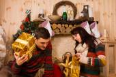 Young man and woman opening their Xmas gifts — Stock Photo