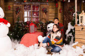 Young Couple Sitting on Christmas Decorated House — Stock Photo