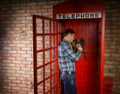 Man making a call in a red telephone booth — Stock Photo
