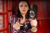 Woman pointing to a vintage telephone handset — Stock Photo