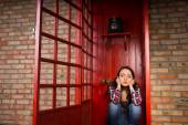 Troubled Woman Crouching in Red Telephone Booth — Stock Photo
