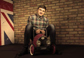 Happy Young Man Sitting on Vintage Toy Car — Stock Photo
