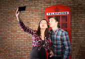 Couple taking a selfie with a British phone booth — Stock Photo