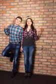 Young White Couple Posing at Brick Wall — Stock Photo