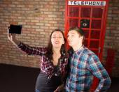 Tourists posing in front of a British phone booth — Stockfoto