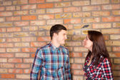 Smiling Couple Facing Each Other near Brick Wall — Stock Photo
