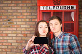 Couple posing in front of a British phone booth — Stock Photo